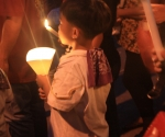 A Little Boy Holding A Candle