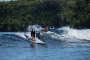 Surfers Riding the Waves in Siargao